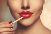 Frau, die sich die Lippen schminkt