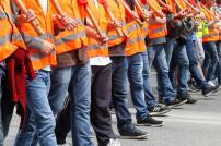 Streikende in Warnwesten laufen in einer Reihe