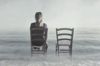 Eine Frau auf einem Stuhl. Neben ihr ein leerer Stuhl
