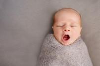 Gähnendes Baby in Decke