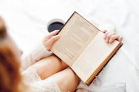 Lady liest Buch und trinkt Kaffee