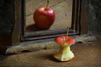 Verkehrtes Spiegelbild: Ein Apfel vor einem Spiegel