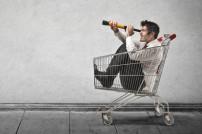 Mann in Einkaufswagen mit Fernglas in der Hand