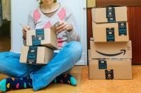 Frau sitzt mit Amazon-Paketen auf dem Boden
