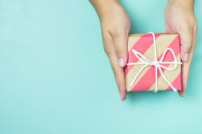Kleines Geschenk wird von zwei Händen gehalten