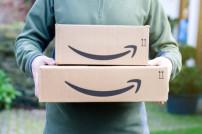Mann trägt zwei Amazon-Pakete