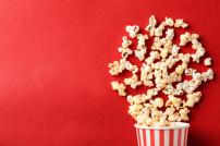 Popcorn-Becher auf rotem Hintergrund