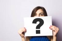 Frau mit Fragezeichen-Schild