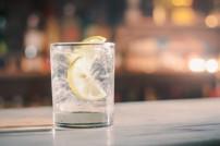 Glas mit klarer Flüssigkeit, Zitrone und Eiswürfeln