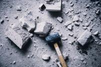 Hammer mit vielen Gesteinsbrocken drum herum