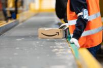 Amazon-Logistik-Mitarbeiter mit Paket an einem Fließband