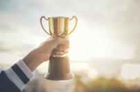 Gewinner mit einem Pokal in der Hand