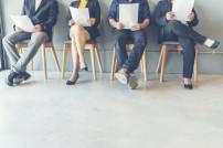 Bewerbung um Jobs: Verschiedene Menschen, die auf Stühlen sitzen