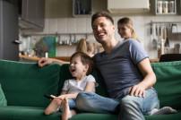 Menschen lachen vor dem TV