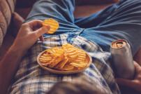 Binge Watching: Mann liegt in einem Sessel und isst Chips