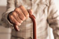 Älterer Mensch: Hände auf Gehstock