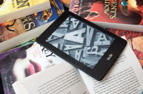 Amazon Kindle E-Book-Reader auf einem Haufen Bücher