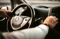 Mann am Steuer eines Autos der Marke Nissan