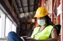 Arbeiterin schaut auf Handy