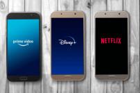 Drei Smartphones mit verschiedenen Streaming-Diensten auf den Bildschirmen