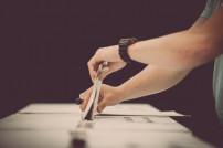 Wahlzettel wird in Urne gesteckt