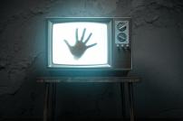 Horrorfilm: Dunkle Hand in einem Fernseher