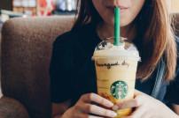 Frau trinkt Kaffee-Getränk von Starbucks