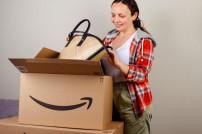 Frau packt fröhlich ein Paket aus, das online bestellt wurde