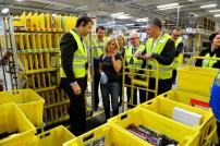 Amerikanischer Generalkonsul erkundigt sich bei eine Amazon Mitarbeiterin nach ihrer Tätigkeit