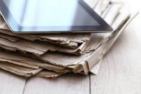 Tablet auf einem Stapel Zeitungen