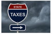 Schild vor bewölktem Himmel mit Aufschrift State Taxes
