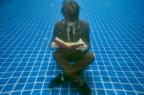 Mann liest Buch unter Wasser